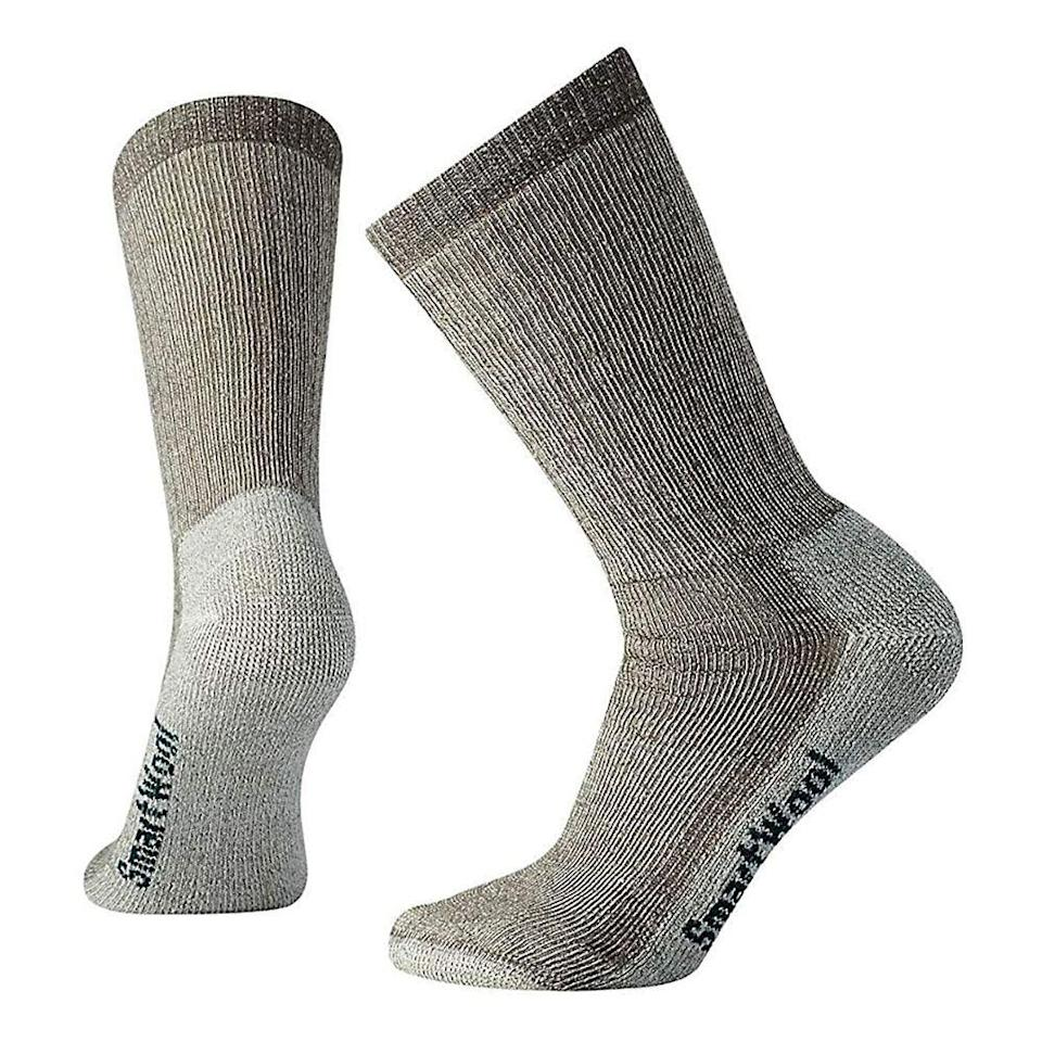 """<p><strong>Smartwool</strong></p><p>amazon.com</p><p><strong>$15.16</strong></p><p><a href=""""https://www.amazon.com/dp/B000SMXVUG?tag=syn-yahoo-20&ascsubtag=%5Bartid%7C2141.g.32869392%5Bsrc%7Cyahoo-us"""" rel=""""nofollow noopener"""" target=""""_blank"""" data-ylk=""""slk:Shop Now"""" class=""""link rapid-noclick-resp"""">Shop Now</a></p><p>Smartwool socks are extremely comfortable and versatile—we guarantee these won't <em>only</em> be used for hiking! Made with a blend of Merino wool, nylon, and elastane, these insulated socks regulate body temperature and keep feet warm while also removing sweat when active. Another great feature? These have a thick layer of cushion at the bottom to absorb impact while walking. </p>"""