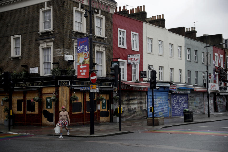 A man walks past temporarily closed shops and a pub in Camden Town, an area of London usually bustling with tourists and visitors to its market, Tuesday, Jan. 12, 2021, during England's third national lockdown since the coronavirus outbreak began. Britain, with over 81,000 dead, has the deadliest virus toll in Europe and the number of hospital beds filled by COVID-19 patients has risen steadily for more than a month. (AP Photo/Matt Dunham)