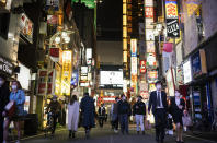 People walk through a street filled with entertainment, restaurants and bars in the Shinjuku neighborhood of Tokyo on Friday, April 9, 2021. Japan announced Friday that it will raise the coronavirus alert level in Tokyo to allow tougher measures to curb the rapid spread of a more contagious variant ahead of the Summer Olympics. (AP Photo/Hiro Komae)