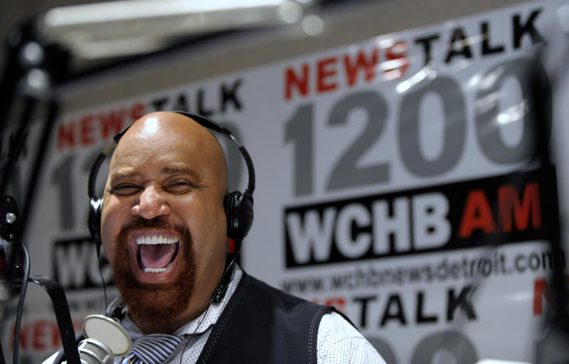 """In this Oct. 16, 2013 photo, radio host Angelo Henderson laughs with Detroit Mayoral Candidate Mike Duggan and his guest Impact Church Pastor Keenan Knox on Henderson's show called, """"Your Voice."""" A medical examiner's spokesman said Henderson, Pulitzer prize-winning Detroit journalist, radio host and co-founder of a prominent community patrol group, died Saturday, Feb. 15, 2014. (AP Photo/Detroit News, Todd McInturf) DETROIT FREE PRESS OUT; HUFFINGTON POST OUT"""