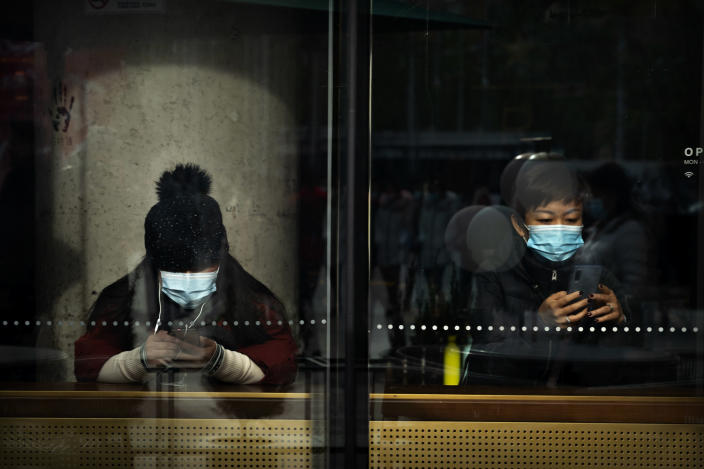 People wearing face masks to protect against the coronavirus sit in a coffee shop in Beijing, Saturday, Nov. 28, 2020. (AP Photo/Mark Schiefelbein)