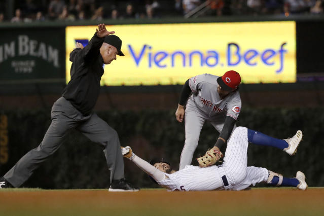 Second base umpire Jeff Nelson calls Chicago Cubs' Nicholas Castellanos safe at second as Cincinnati Reds' Alex Blandino applies a tag during the fourth inning of a baseball game Wednesday, Sept. 18, 2019, in Chicago. (AP Photo/Charles Rex Arbogast)