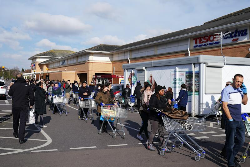 People queue at a Tesco Extra in Osterley, London, the day after Tesco announced their stores will now have a designated hour for NHS staff to purchase their food shops. (Photo by John Walton/PA Images via Getty Images)