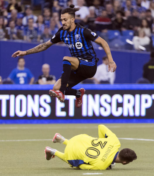Montreal Impact's Maximiliano Urruti leaps over New England Revolution goalkeeper Matt Turner during the first half of an MLS soccer game in Montreal, Saturday, Feb. 29, 2020. (Graham Hughes/The Canadian Press via AP)