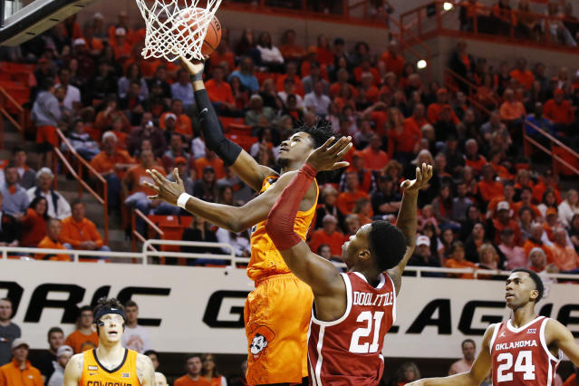 Oklahoma State forward Kalib Boone, center left, shoots in front of Oklahoma forward Kristian Doolittle (21) in the first half of an NCAA college basketball game in Stillwater, Okla., Saturday, Feb. 22, 2020. (AP Photo/Sue Ogrocki)