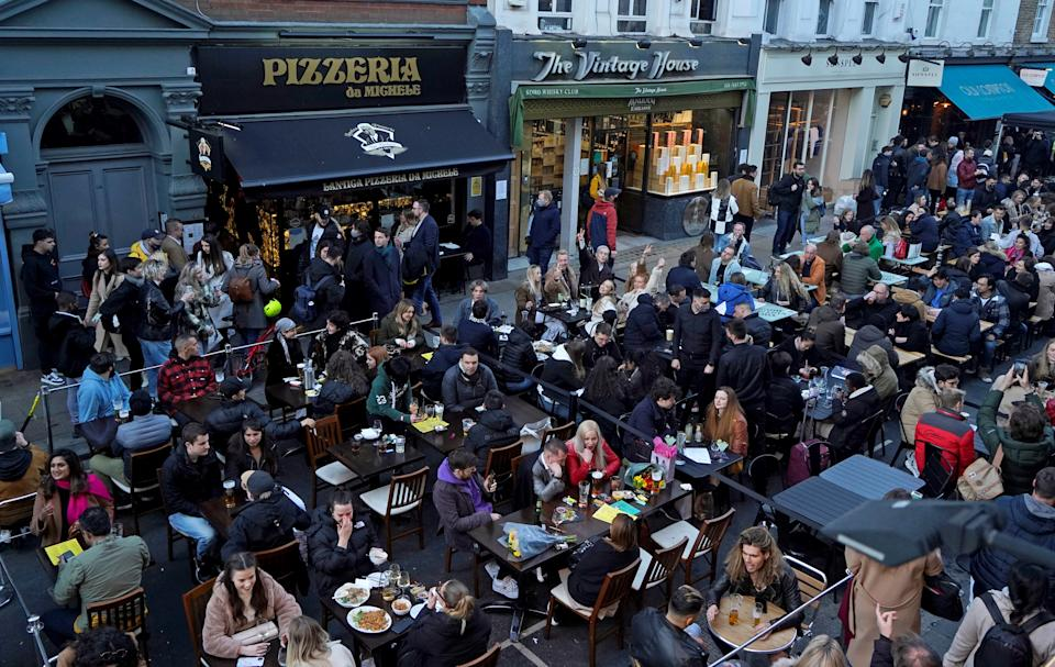 People sit at outside tables to eat and drink at re-opened bars and restaurants, in the street in the Soho area of London, on April 16, 2021 following step two of the government's roadmap out of England's third national lockdown. - Britons on Apri l12 toasted a significant easing of coronavirus restrictions, with early morning pints -- and much-needed haircuts -- as the country took a tentative step towards the resumption of normal life. Businesses including non-essential retail, gyms, salons and outdoor hospitality were all able to open for the first time in months in the second step of the government's roadmap out of lockdown. (Photo by Niklas HALLE'N / AFP) (Photo by NIKLAS HALLE'N/AFP via Getty Images)
