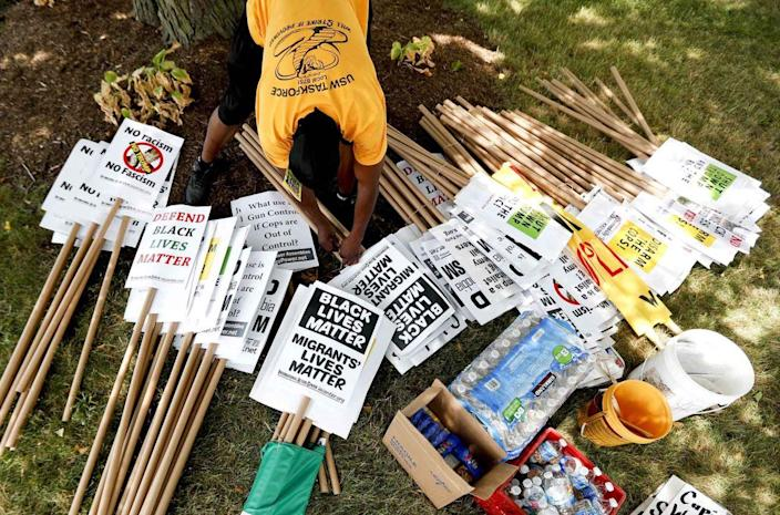 <p>A demonstrator organizes protest signs on July 17, 2016, in Cleveland, Ohio, in preparation for the Republican National Convention. (Photo: John Minchillo/AP)</p>