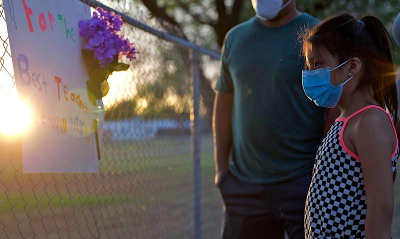 Ximena Colecio looks at a sign she hung on a fence outside her school in Del Rio, TX on Wednesday, July 22, 2020 to remember her teacher who died the day before from COVID-19.