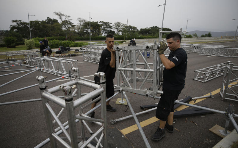 """Workers build the stage for the upcoming """"Venezuela Aid Live"""" concert at the Tienditas International Bridge on the outskirts of Cucuta, Colombia, on the border with Venezuela, Monday, Feb. 18, 2019. Billionaire Richard Branson is organizing the concert on Feb. 22 featuring Spanish-French singer Manu Chao, Mexican band Mana, Spanish singer-songwriter Alejandro Sanz and Dominican artist Juan Luis Guerra. (AP Photo/Fernando Vergara)"""