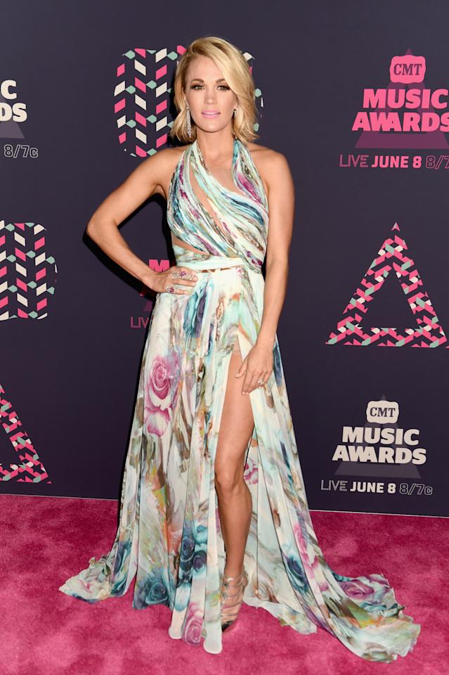 <p>Call Carrie Underwood the queen of country music red carpets. Looking ridiculously fresh in a summer frock, the singer showed a lot of leg with a thigh-high slit. She paired the futuristic piece with diamond drop earrings and multiple diamond rings. Her pink lipstick added a fun pop of color and a brown smoky eye kept things cool. <i>(Photo: Getty Images)</i></p>