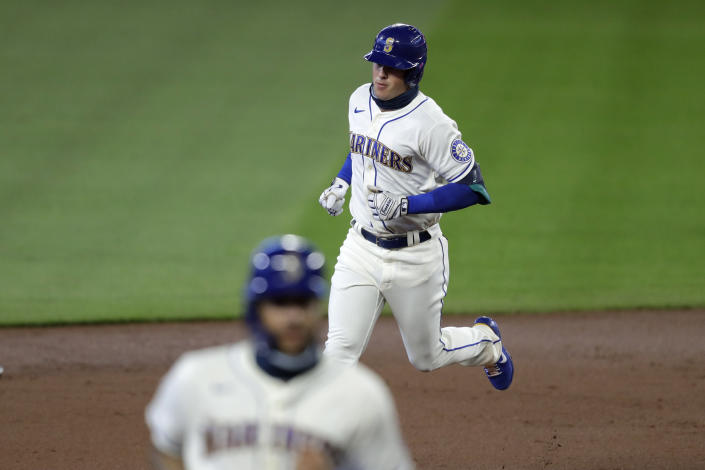 Seattle Mariners' Dylan Moore, top, follows J.P. Crawford around the bases after hitting a two-run home run against the Colorado Rockies in the first inning of a baseball game Sunday, Aug. 9, 2020, in Seattle. (AP Photo/Elaine Thompson)
