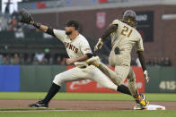 San Diego Padres' Fernando Tatis Jr., right, beats the throws to first base on his base hit next to San Francisco Giants first baseman Brandon Belt during the first inning of a baseball game in San Francisco, Wednesday, Sept. 15, 2021. Tatis Jr. and other players are wearing number 21 in honor of Roberto Clemente Day. (AP Photo/Jeff Chiu)