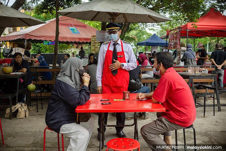 Former pilot Azrin Mohamad Zawawi, 44 and wife Latun Noralyani Meor Aminuddin, 41, run a small 'Kapten Corner' food stall selling local food together with other family members at Boomtown USJ, Selangor on Nov 4, 2020. Captain Azrin, a former Malindo airline pilot, lost his job after he was retrenched along with 2,200 other crew and staff.