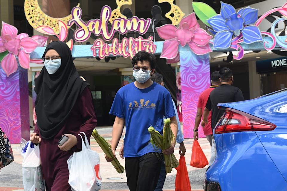 People wearing face masks amid concern over the spread of the COVID-19 coronavirus crosses a road with building displays of festive decorations ahead of Eid al-Fitr which marks the end of the Muslim holy month of Ramadan, at the Geylang Serai market in Singapore on May 21, 2020. (Photo by Roslan RAHMAN / AFP) (Photo by ROSLAN RAHMAN/AFP via Getty Images)