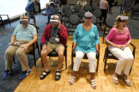Residents of John Knox Village wear goggles as they participate in a virtual reality study, Tuesday, June 1, 2021, in Pompano Beach, Fla. The senior community is in partnership with Stanford University's Virtual Human Interaction Lab on a study to see how older adults respond to virtual reality and whether it can improve their sense of wellbeing. From left to right are Bruce Voelkel, John Dalsimer, Andrea Hipskind, and Janet Anding. (AP Photo/Lynne Sladky)