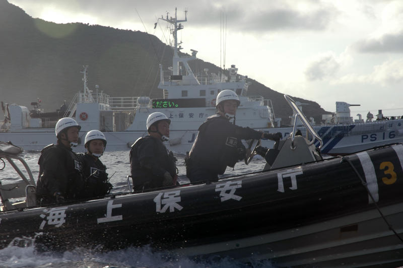 Japanese Coast Guard members on boat sails alongside Japanese activists' fishing boat, not in photo, warning the activists away from a group of disputed islands called Diaoyu by China and Senkaku by Japan, early Sunday, Aug. 18, 2013. Nearly two dozen Japanese nationalist activists and fishermen have sailed to a small group of islands at the center of a territorial dispute with China. They were closely monitored by Japan's Coast Guard, but there were no Chinese patrols in the area and no incidents were reported. (AP Photo/Emily Wang)