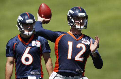 Denver Broncos quarterback Paxton Lynch, front, throws during drills as quarterback Chad Kelly looks on at the NFL football team's training camp Wednesday, June 13, 2018, in Englewood, Colo. (AP Photo/David Zalubowski)