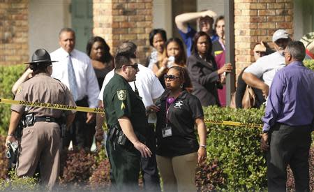 Parents wait behind as police consult after several children were injured after being struck by a vehicle at a KinderCare Learning Center in Winter Park