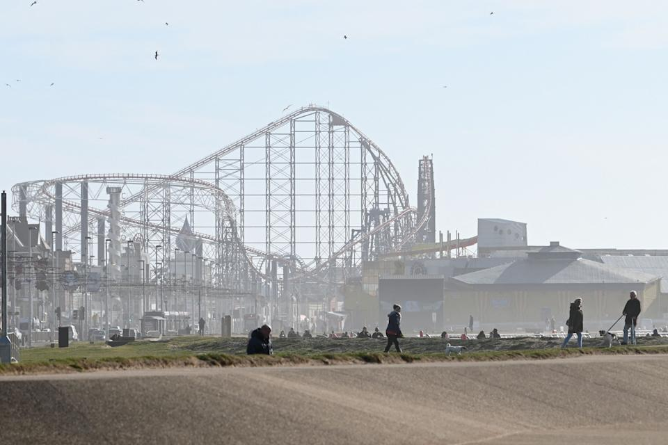 People enjoy the winter sunshine on the beach-front near the Blackpool Pleasure Beach amusement park in Blackpool, Lancashire on March 16, 2021, with the Big One roller coaster looming in the background. (Photo by Paul ELLIS / AFP) (Photo by PAUL ELLIS/AFP via Getty Images)