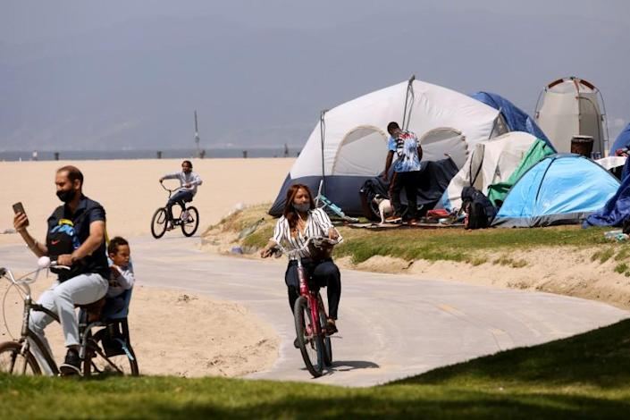 VENICE, CA - APRIL 16, 2021 - - Bicyclists ride past several homeless tents along the bike path in Venice on April 16, 2021. (Genaro Molina / Los Angeles Times)