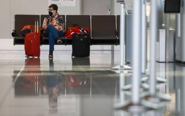 A passenger sits at the Calgary Airport on Oct. 30. Kandola said she's looking into shorter quarantine periods for vaccinated individuals.