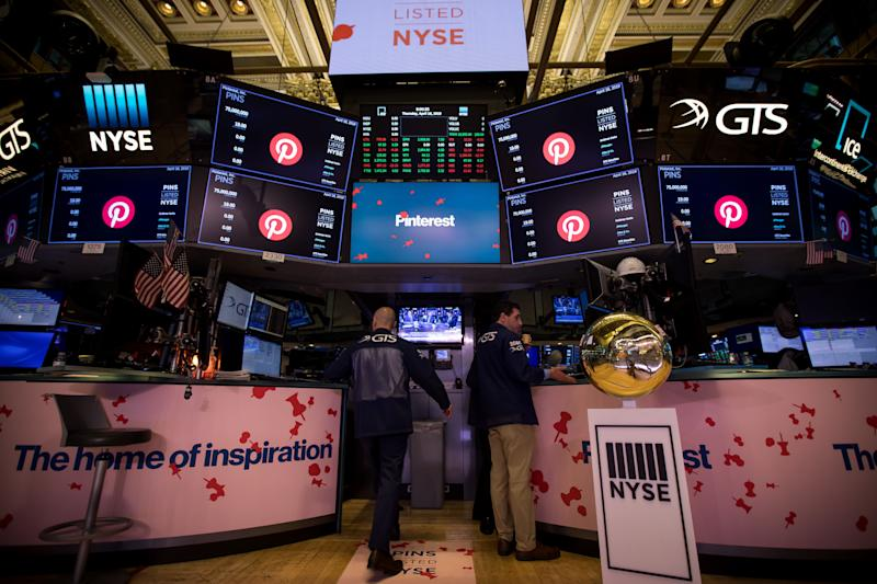Traders work beneath monitors displaying Pinterest Inc. signage during the company's initial public offering (IPO) on the floor of the New York Stock Exchange (NYSE) in New York, U.S., on Thursday, April 18, 2019. Pinterest's message to investors was don't compare us to social media or a search engine. The outcome Wednesday was that it raised about $1.4 billion in an above-range initial public offering. Photographer: Michael Nagle/Bloomberg via Getty Images