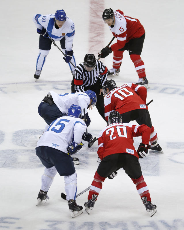 Team Finland and team Austria face off at the start of a men's ice hockey game at the 2014 Winter Olympics, Thursday, Feb. 13, 2014, in Sochi, Russia. (AP Photo/Mark Humphrey)