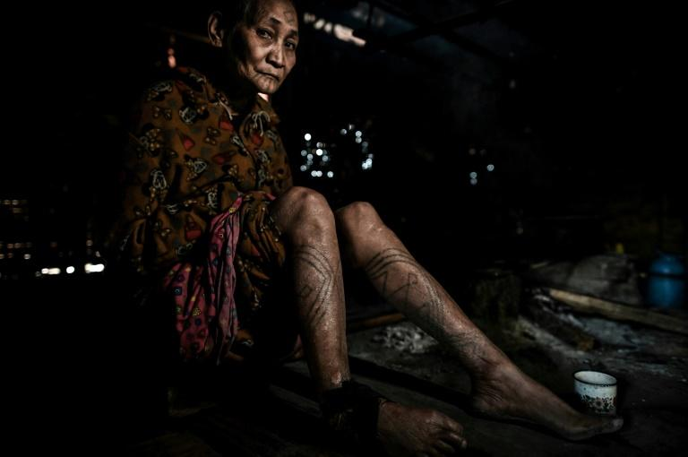 The Naga tribes in Myanmar's far north would use a thorn to drive tree sap under the warrior's skin to ink a permanent reminder of his headhunting prowess -- and his family would often follow suit (AFP Photo/Ye Aung THU)