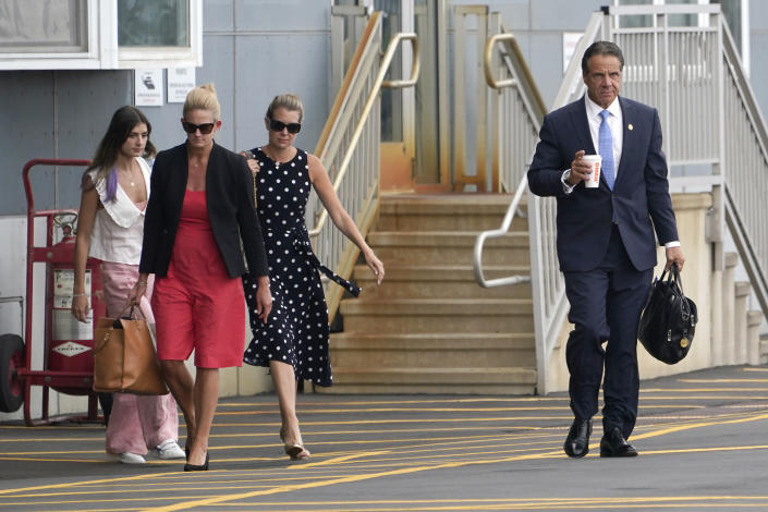 New York Gov. Andrew Cuomo, right, is followed by his daughter Michaela Kennedy Cuomo, from left, Office Director Stephanie Benton and former Executive Secretary Melissa DeRosa as they prepare to board a helicopter after announcing Cuomo's resignation, Tuesday, Aug. 10, 2021, in New York. Cuomo says he will resign over a barrage of sexual harassment allegations. The three-term Democratic governor's decision, which will take effect in two weeks, was announced as momentum built in the Legislature to remove him by impeachment. (AP Photo/Seth Wenig)