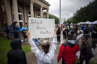 FILE - In this Thursday, June 4, 2020, file photo, a group of protesters gather outside the Glynn County Courthouse while a preliminary hearing is being held inside for Travis McMichael, Gregory McMichael and William Bryan, in Brunswick, Ga. The three are accused of shooting of Ahmaud Arbery while he ran through their neighborhood in February. The Glynn County commissioners are suing to stop a referendum on abolishing the county police department. State lawmakers approved the binding referendum in the spring after the February shooting death of Arbery. (AP Photo/Stephen B. Morton, File)