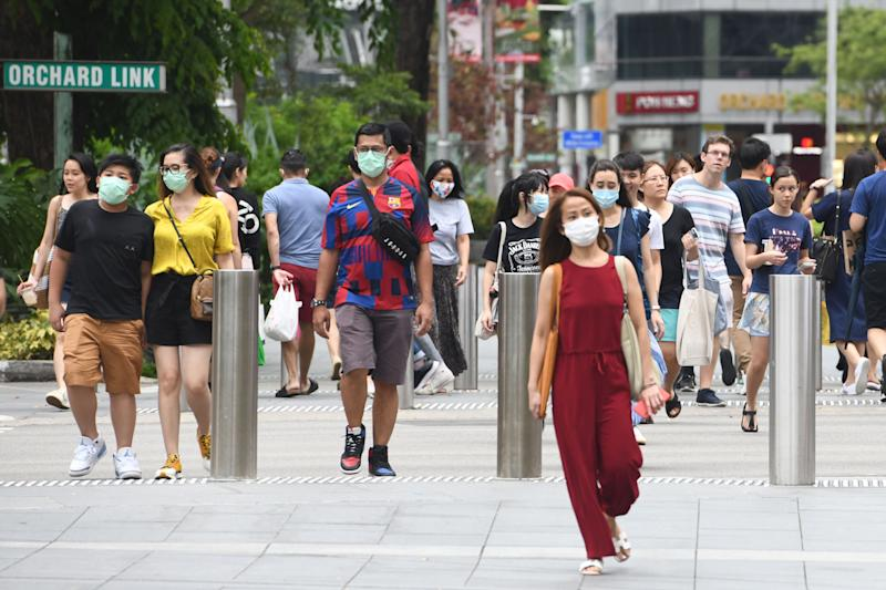 People wear facemasks to try to halt the spread of the COVID-19 coronavirus as they walk through a shopping district on Orchard Road in Singapore on April 5, 2020. (Photo by ROSLAN RAHMAN / AFP) (Photo by ROSLAN RAHMAN/AFP via Getty Images)