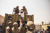 In this image courtesy of the US Central Command Public Affairs, British and Turkish coalition forces, and US Marines assist a child during an evacuation at Hamid Karzai International Airport in Kabul on August 20, 2021