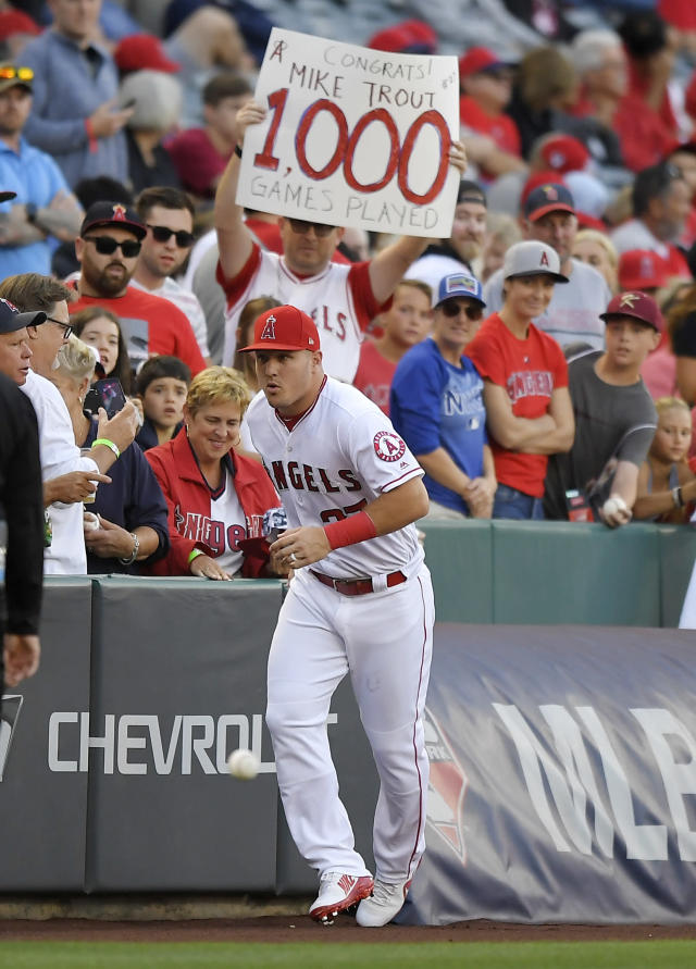 Los Angeles Angels' Mike Trout runs to the dugout after signing autographs as a fan holds up a sign congratulating him on his 1,000th game played, prior to the team's baseball game against the Toronto Blue Jays Thursday, June 21, 2018, in Anaheim, Calif. (AP Photo/Mark J. Terrill)