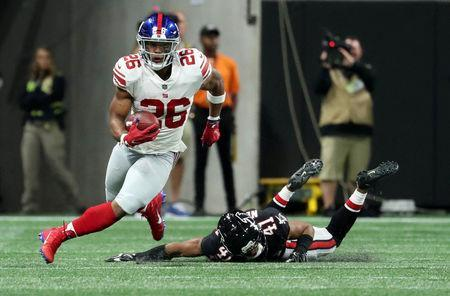 Oct 22, 2018; Atlanta, GA, USA; New York Giants running back Saquon Barkley (26) runs after a catch against Atlanta Falcons defensive back Sharrod Neasman (41) in the first quarter at Mercedes-Benz Stadium. Mandatory Credit: Jason Getz-USA TODAY Sports