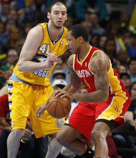 Houston Rockets center Greg Smith, front, works ball inside for a shot as Denver Nuggets forward Kosta Koufos covers in the third quarter of an NBA basketball game in Denver on Saturday, April 6, 2013. (AP Photo/David Zalubowski)