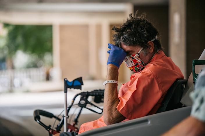 A man sits with his head down while waiting to depart the Houston Methodist Hospital on July 16. (Brandon Bell/Getty Images)