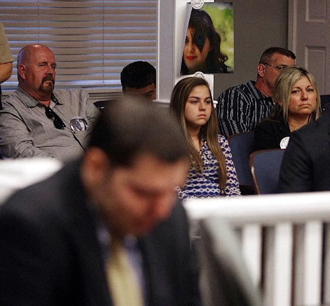 A photo of Tiffany York hangs in court Thursday May 1, 2014, in Ludowici, Ga., as her mother Brenda Thomas, right, and her daughter Kendell Thomas, listen to the court proceedings of Army Sgt Anthony Peden who plead guilty to the slaying of Tiffany York. Peden was sentenced to life in prison Thursday by a southeast Georgia judge for the December 2011 slayings of 17-year-old Tiffany York and her boyfriend, former soldier Michael Roark. (AP Photo/Lewis Levine)