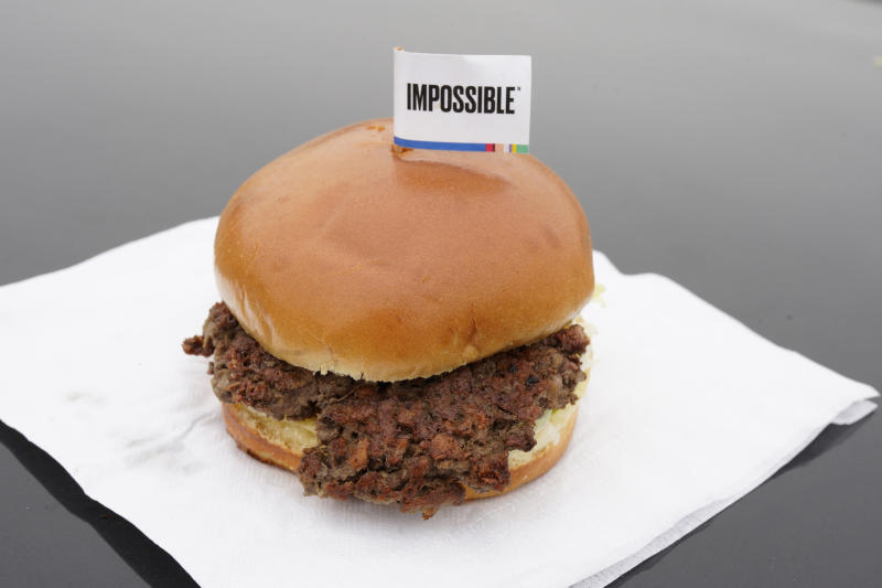 FILE- This Jan. 11, 2019, file photo shows the Impossible Burger in Bellevue, Neb. After months of shortages, Impossible Foods is partnering with a veteran food production company to ramp up supplies of its popular plant-based burgers. (AP Photo/Nati Harnik, File)
