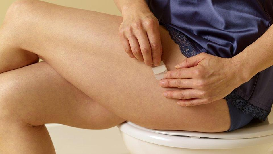 Hormonal Replacement Therapy - woman applying a patch on her leg.