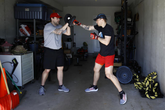 Fighter Kyle Daukaus, right, trains with his brother Chris Daukaus in their garage, Saturday, May 2, 2020, in Philadelphia. Kyle, a rising star in the regional MMA promotion Cage Fury Fighting Championships, is still chasing his dream of getting the call to fight for UFC despite the coronavirus pandemic. (AP Photo/Matt Slocum)