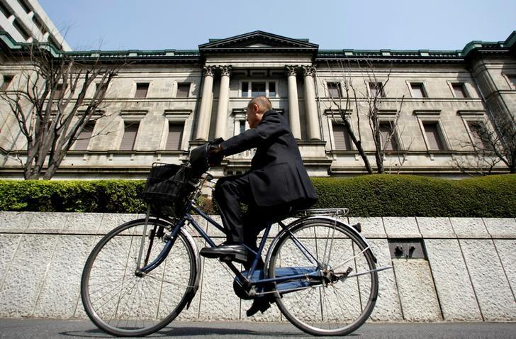 FILE PHOTO: A man rides a bicycle past the BOJ building in Tokyo