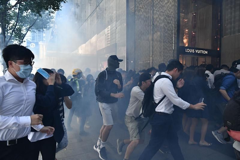 People react after tear gas was fired by police during a protest in Hong Kong on November 11, 2019. | ANTHONY WALLACE—AFP via Getty Images