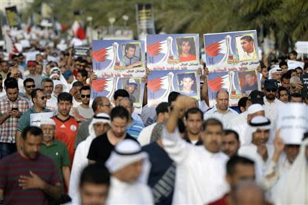Protesters hold banners as they shout anti-government slogans during a protest in Budaiya west of Manama, April 4, 2014. REUTERS/Stringer