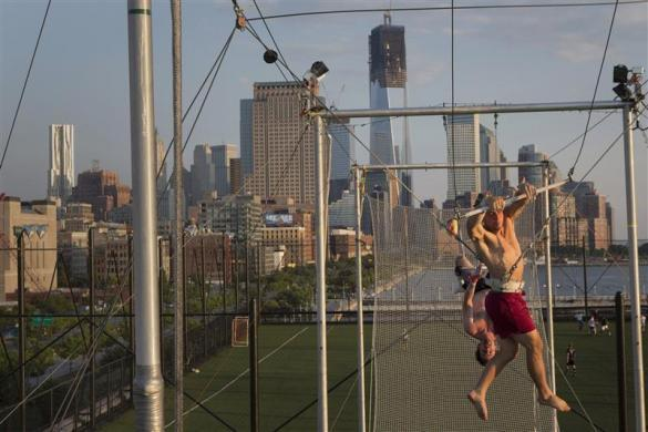 Greg Cooper (foreground) makes a return after being caught by Josh Cohen at Trapeze School New York July 1, 2012.