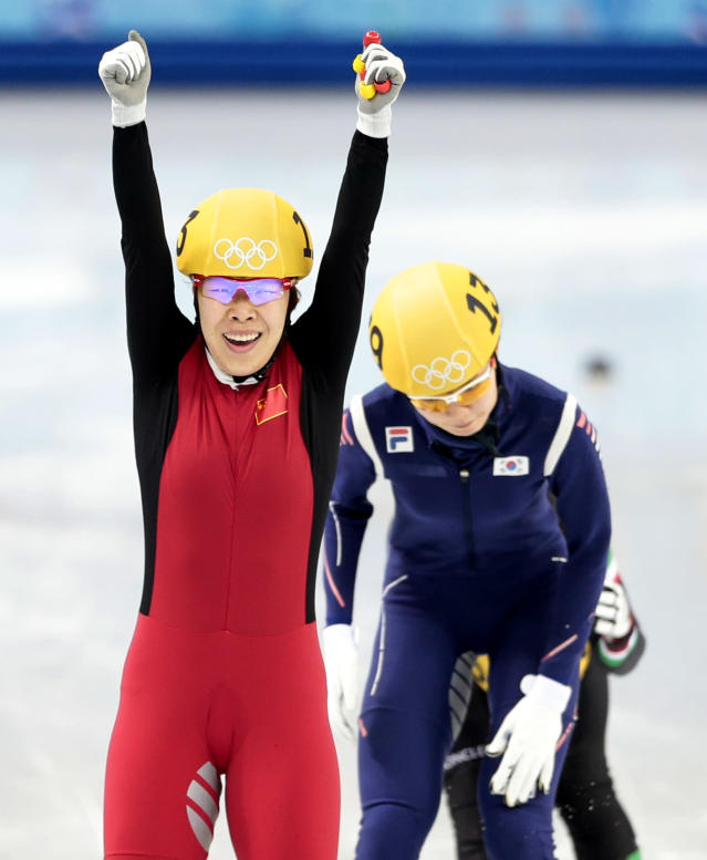 Zhou Yang of China, left, reacts as she crosses the finish line first ahead of Shim Suk-Hee of South Korea, right, in a women's 1500m short track speedskating final at the Iceberg Skating Palace during the 2014 Winter Olympics, Saturday, Feb. 15, 2014, in Sochi, Russia. (AP Photo/Ivan Sekretarev)