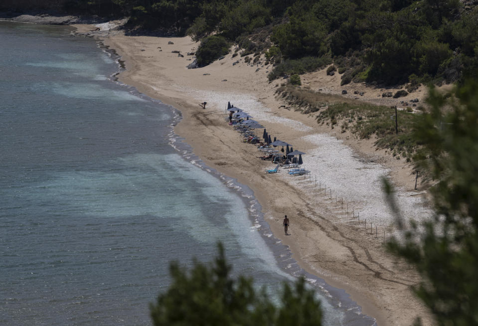 A man walks at the beach of Marathokampos, on the island of Samos, North Aegean, Greece, Wednesday June 9, 2021. An inflatable dinghy carrying nearly three dozen people reached the Greek island of Samos from the nearby Turkish coast. Within 24 hours, refugee rights groups say, the same group was seen drifting in a life raft back to Turkey. But of the 32 people determined to have initially made it to Samos, only 28 were in the raft the Turkish coast guard retrieved at sea. Days later, the missing four, a Palestinian woman and her three children, appeared in Samos' main town, apparently having eluded authorities. (AP Photo/Petros Giannakouris)