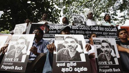 Demonstrators hold placards with an image of missing cartoonist and columnist Prageeth Eknaligoda during a protest in front of the United Nations head office in Colombo