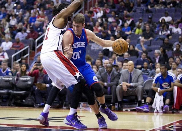 Philadelphia 76ers center Spencer Hawes (00) drives past Washington Wizards forward Nene during the first half of an NBA basketball game on Monday, Jan. 20, 2014 in Washington. (AP Photo/ Evan Vucci)