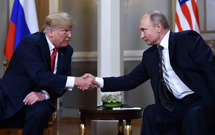 """President Trump and Russian President Vladimir Putin shake hands ahead of their private meeting in Helsinki, Finland, in 2018. <span class=""""copyright"""">(Brendan Smialowski / AFP-Getty Images)</span>"""