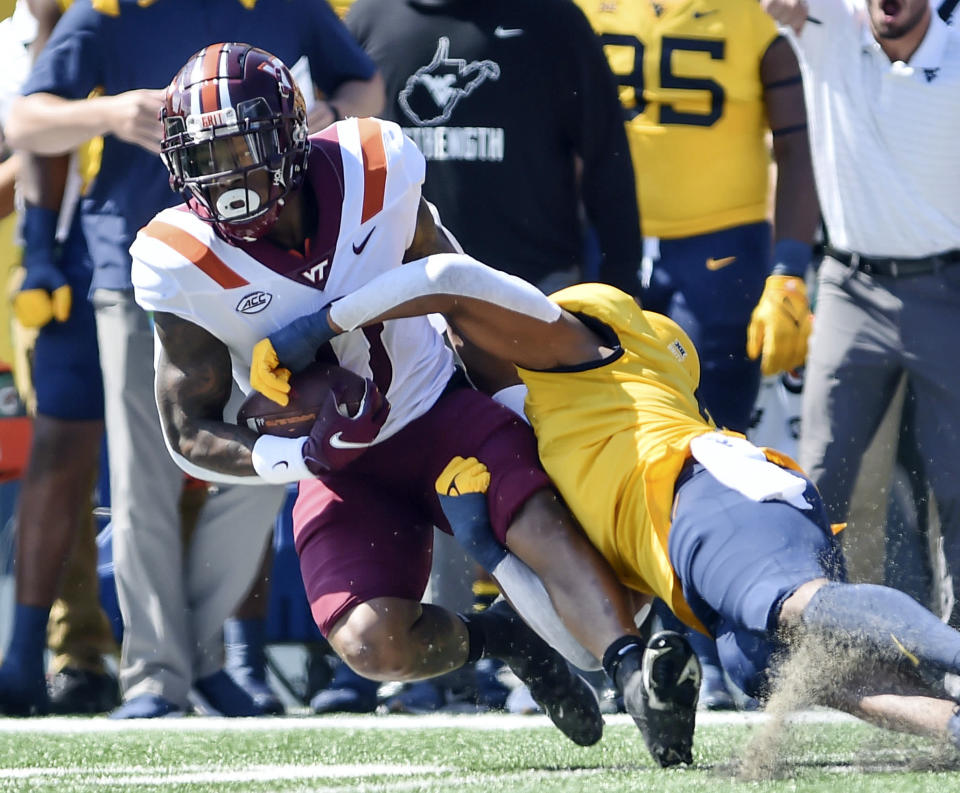 Virginia Tech's Jalen Holston, left, is tackled by West Virginia's Lance Dixon during the first half of an NCAA college football game in Morgantown, W.Va., Saturday, Sept. 18, 2021. (AP Photo/William Wotring)